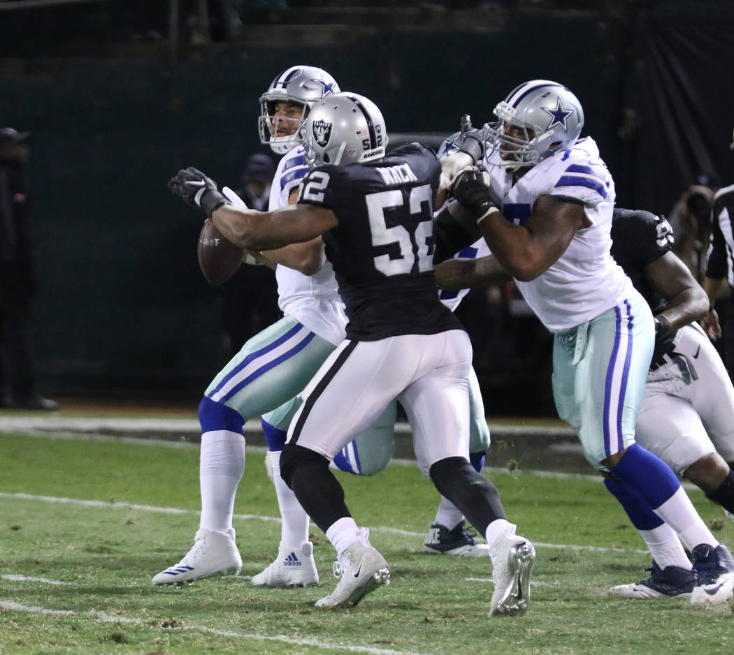 Oakland Raiders defensive end Khalil Mack (52) comes in to pressure Dallas Cowboys quarterback Dak Prescott (4) as offensive tackle Tyron Smith (77) tries to prevent a sack during the first half o ...