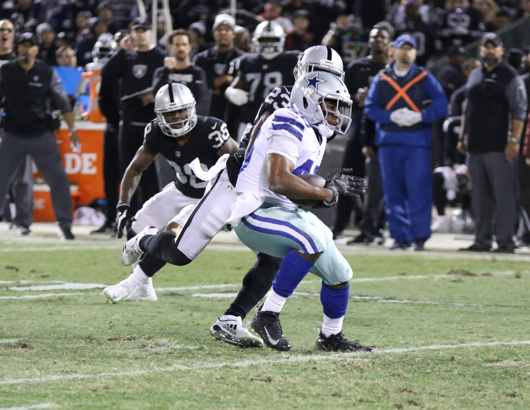 Dallas Cowboys running back Alfred Morris (46) runs past Oakland Raiders cornerback Dexter McDonald (23) during the first half of a NFL game in Oakland, Calif., Sunday, Dec. 17, 2017. Heidi Fang L ...