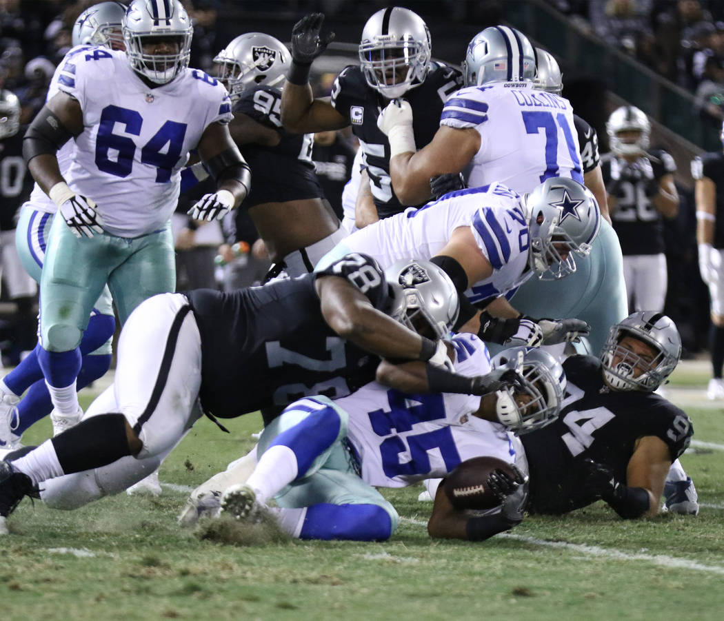 Dallas Cowboys running back Rod Smith (45) is tackled by Oakland Raiders defensive tackle Justin Ellis (78) after a run during the first half of a NFL game in Oakland, Calif.., Sunday, Dec. 17, 20 ...