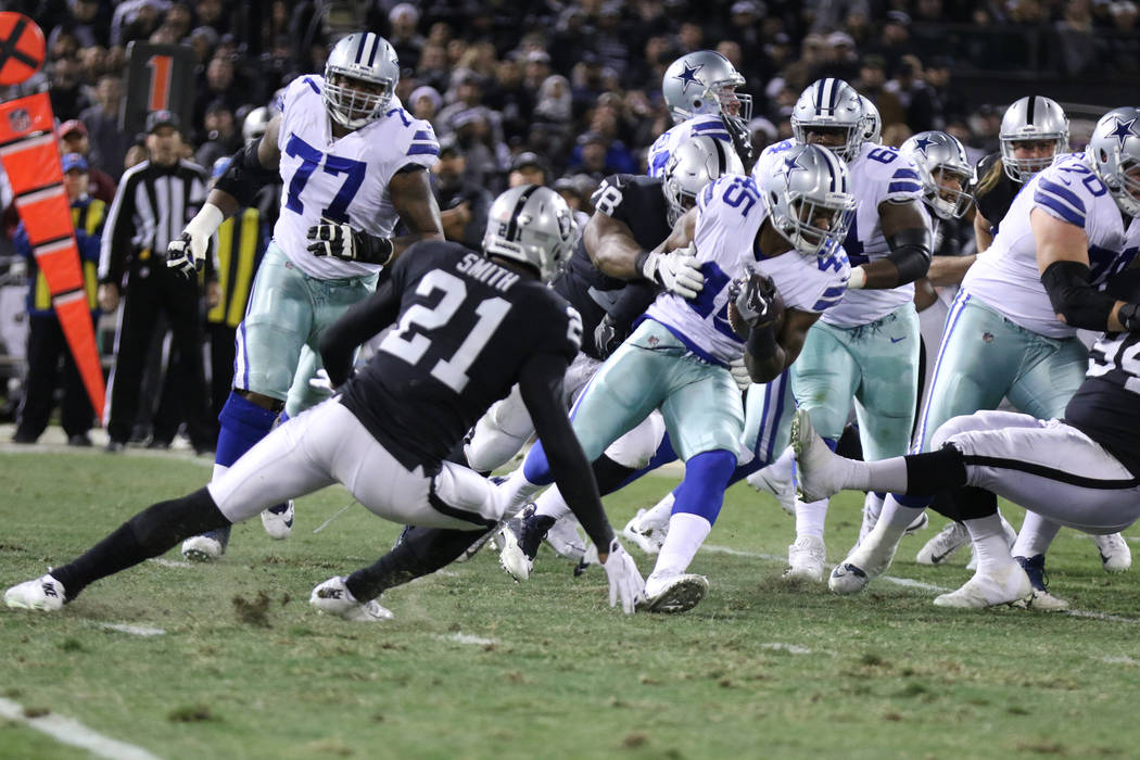 Dallas Cowboys running back Rod Smith (45) rushes with the football as Oakland Raiders defensive tackle Justin Ellis (78) comes in for a tackle during the first half of a NFL game in Oakland, Cali ...