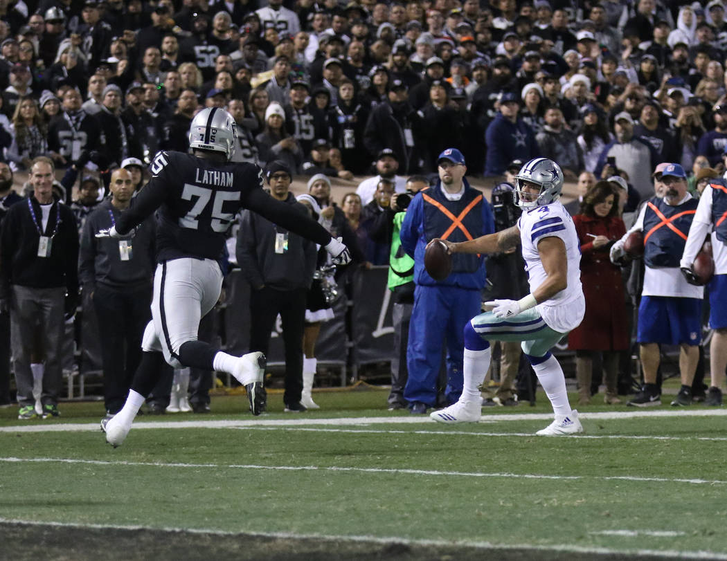 Dallas Cowboys quarterback Dak Prescott (4) rushes toward the end zone during the first half of a NFL game as Oakland Raiders defensive tackle Darius Latham (75) closes in in Oakland, Calif., Sund ...