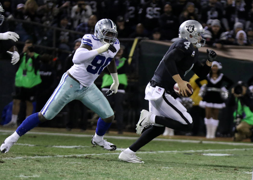 Oakland Raiders quarterback Derek Carr (4) scrambles with the football as Dallas Cowboys defensive end Demarcus Lawrence (90) closes in during the first half of a NFL game in Oakland, Calif., Sund ...