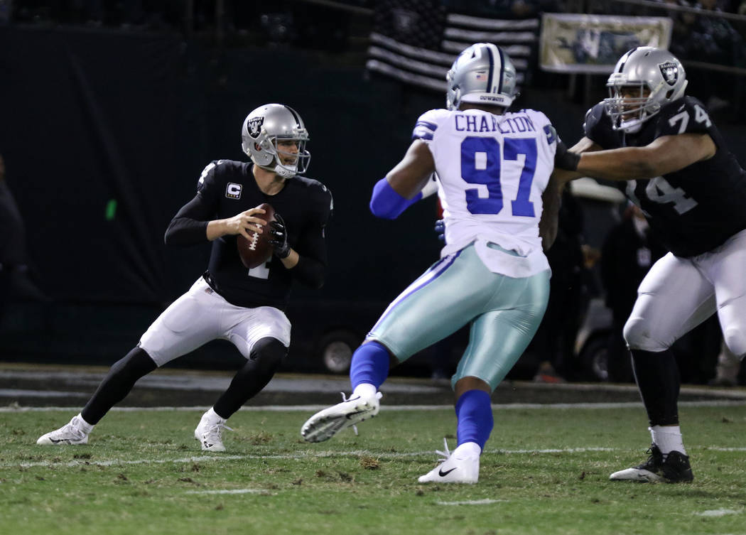 Oakland Raiders quarterback Derek Carr (4) drops back to pass as offensive tackle Vadal Alexander (74) keeps Dallas Cowboys defensive end Taco Charlton (97) at bay during the first half of a NFL g ...