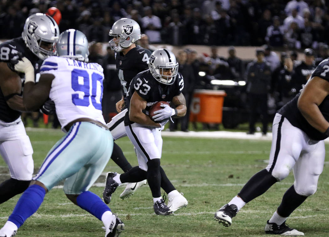 Oakland Raiders running back DeAndre Washington (33) runs with the football against the Dallas Cowboys during the first half of a NFL game in Oakland, Calif., Sunday, Dec. 17, 2017. Heidi Fang Las ...