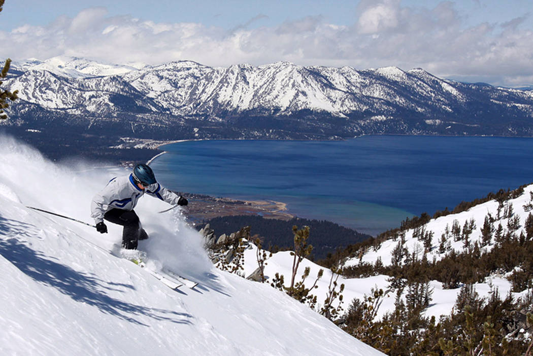 With Lake Tahoe as a backdrop, a skier kicks up some powder at Heavenly Ski Resort in South Lake Tahoe, Calif., in 2010. (AP Photo/Dino Vournas)
