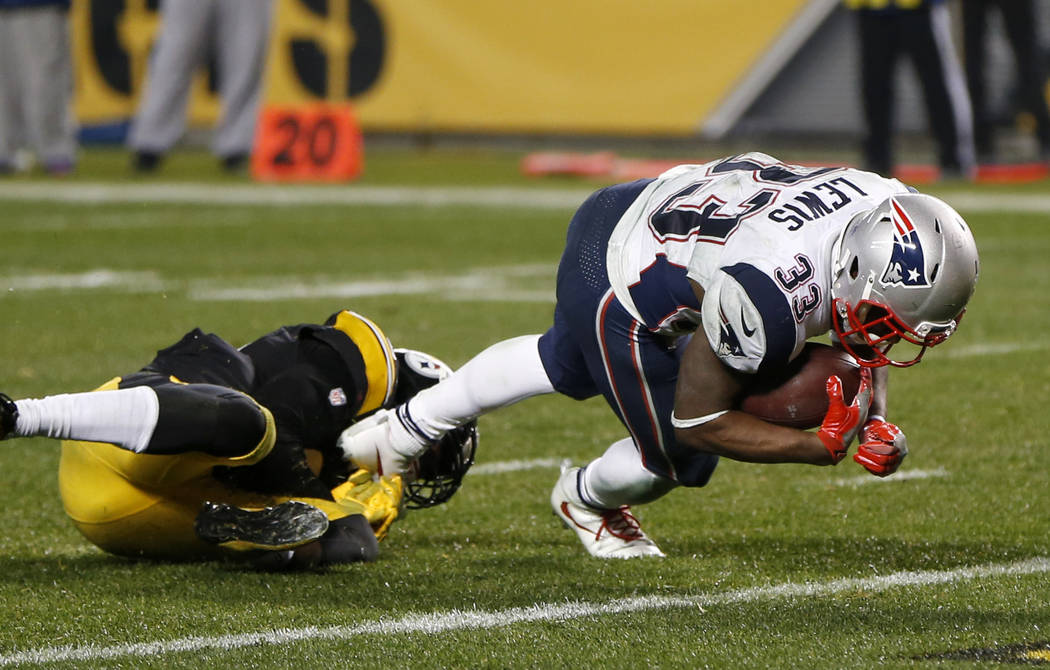 New England Patriots running back Dion Lewis (33) slips the tackle of Pittsburgh Steelers cornerback Artie Burns (25) and dives for the end zone for a touchdown during the second half of an NFL fo ...