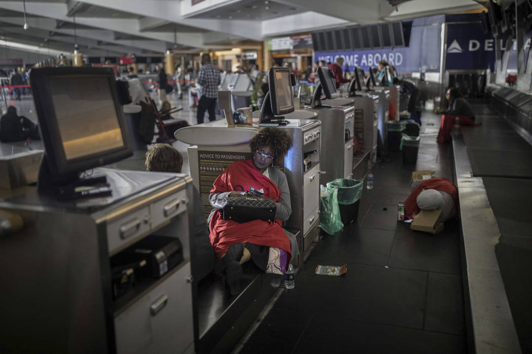 Passengers rest behind the ticket counter after the lights went out at Hartfield-Jackson Atlanta International Airport, Sunday, Dec. 17, 2017, in Atlanta. A sudden power outage at the airport on S ...
