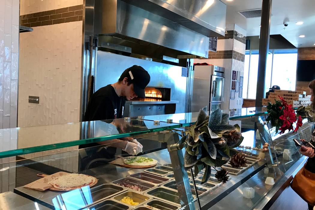 Employees add ingredients to a customer's pizza right in front of them. The pizza is then placed in a stone-bed oven to cook for three minutes. (Madelyn Reese/View) @MadelynGReese