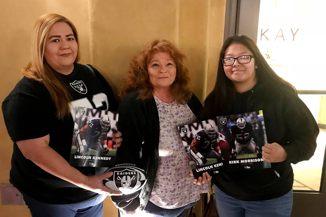 Ernestine Matus, from left, poses with her mother, Rosella, and daughter, Desiree, after donating gifts for the Raiders' Toys for Tots collection in front of the Raider Image store at Town Square  ...
