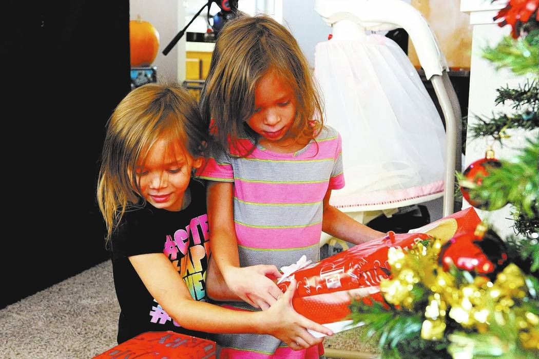 Two of the seven children of Army veteran Larry Hamm, Olivia, 6, left, and Bethannie, 9, arrive home from school to find that the Boot Campaign's Santa Boots program had dropped off presents for t ...