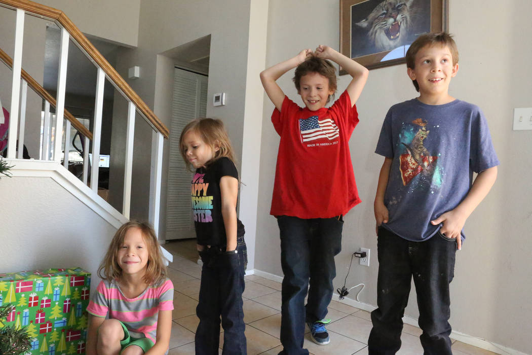 Four of the seven children of Army veteran Larry Hamm, Bethannie, 9, from left, Olivia, 6, Clayton, 11, and Larry, 10, return home from school to find that the Boot Campaign's Santa Boots program  ...