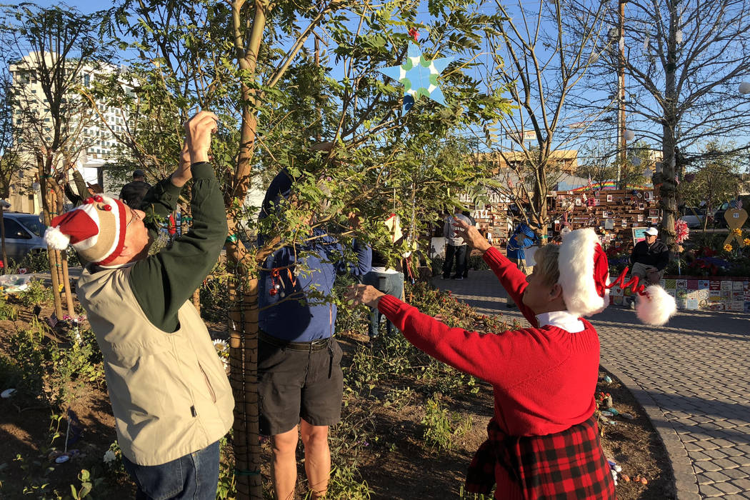Tom Morgan, from left, Michael Fink and Susan Wallace-Morgan string lights on one of 58 trees at Las Vegas Community Healing Garden during the Holidays in the Garden gathering on Saturday, Dec. 9, ...