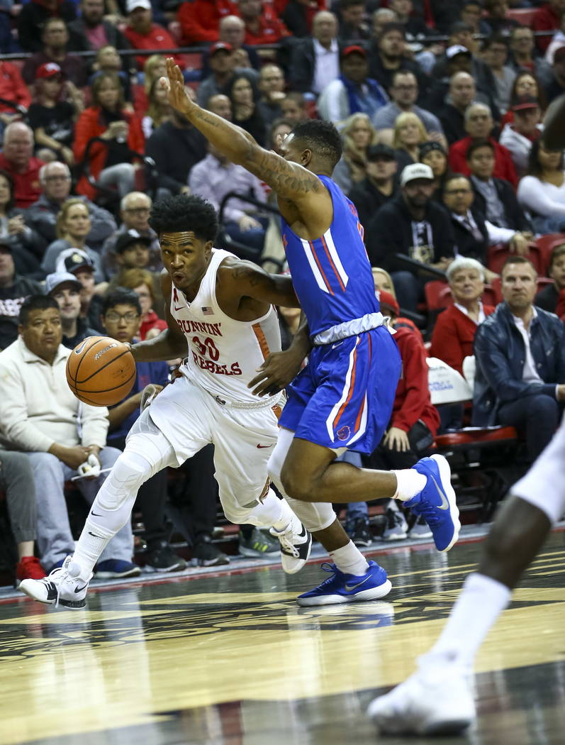 UNLV Rebels guard Jovan Mooring (30) dribbles the ball past Boise State Broncos guard Marcus Dickinson (0) during the first period of an NCAA college basketball game at the Thomas & Mack Cente ...