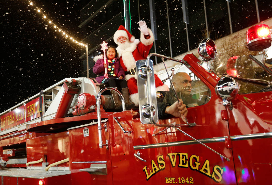 Viridiana Martinez-Ramirez, 8, rides with Santa in a special fire truck provided by Las Vegas Fire & Rescue during the Downtown Summerlin holiday parade in Las Vegas, Monday, Dec. 18, 2017. Fo ...