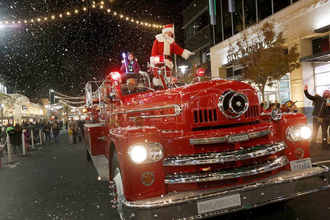 Viridiana Martinez-Ramirez, 8, of Las Vegas rides with Santa in a special fire truck provided by Las Vegas Fire & Rescue during the Downtown Summerlin holiday parade in Las Vegas, Monday, Dec. ...