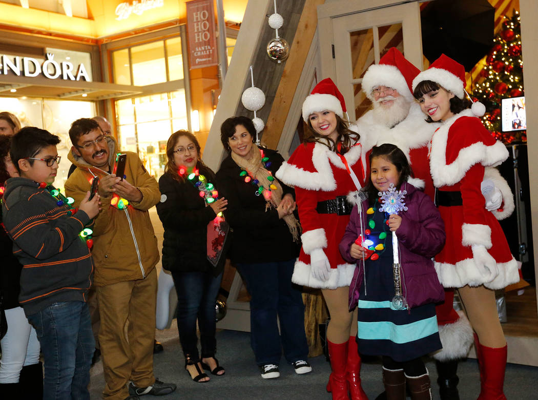 Viridiana Martinez-Ramirez, 8, poses for a photo with Santa after the Downtown Summerlin holiday parade in Las Vegas, Monday, Dec. 18, 2017. Make-A-Wish Southern Nevada and the Howard Hughes Corp. ...