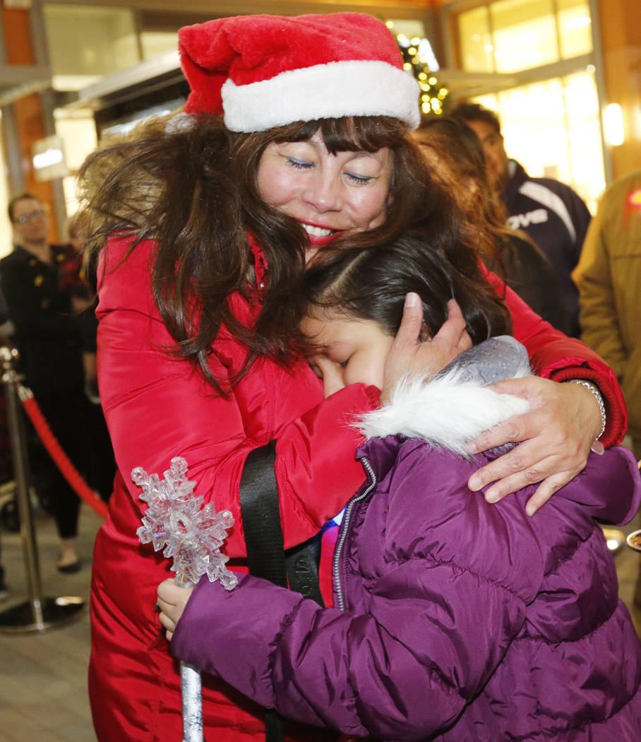 Viridiana Martinez-Ramirez, 9, of Las Vegas, right, hugs her former first grade teacher Balbanera Gonzalez at the Downtown Summerlin in Las Vegas, Monday, Dec. 18, 2017, after she has received the ...