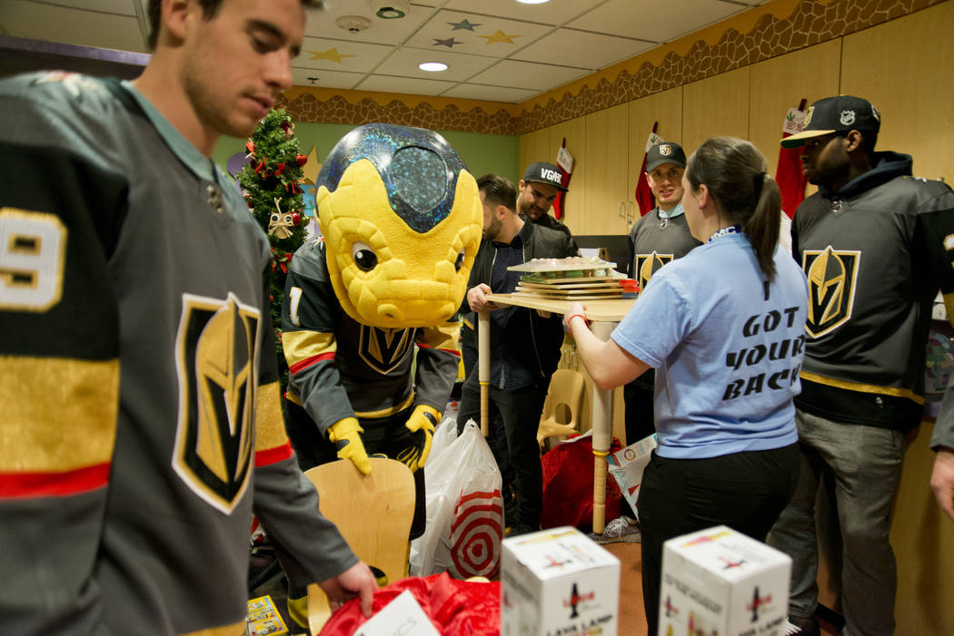 Players for the Vegas Golden Knights and others organize presents for children during an event at the Children's Hospital of Nevada at University Medical Center in Las Vegas on Thursday, Dec. 21,  ...