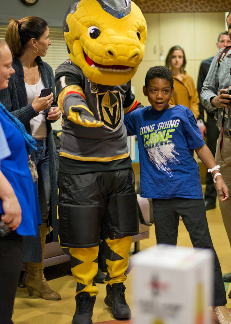 Vegas Golden Knights mascot Chance the Gila Monster shows Deangylo Pollard to a pile of presents during an event at the Children's Hospital of Nevada at University Medical Center in Las Vegas on T ...