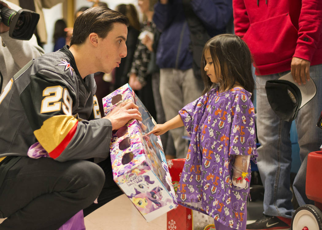 Vegas Golden Knights goaltender Marc-Andre Fleury gives a gift to Elleen Bautista Viveros during an event at the Children's Hospital of Nevada at University Medical Center in Las Vegas on Thursday ...
