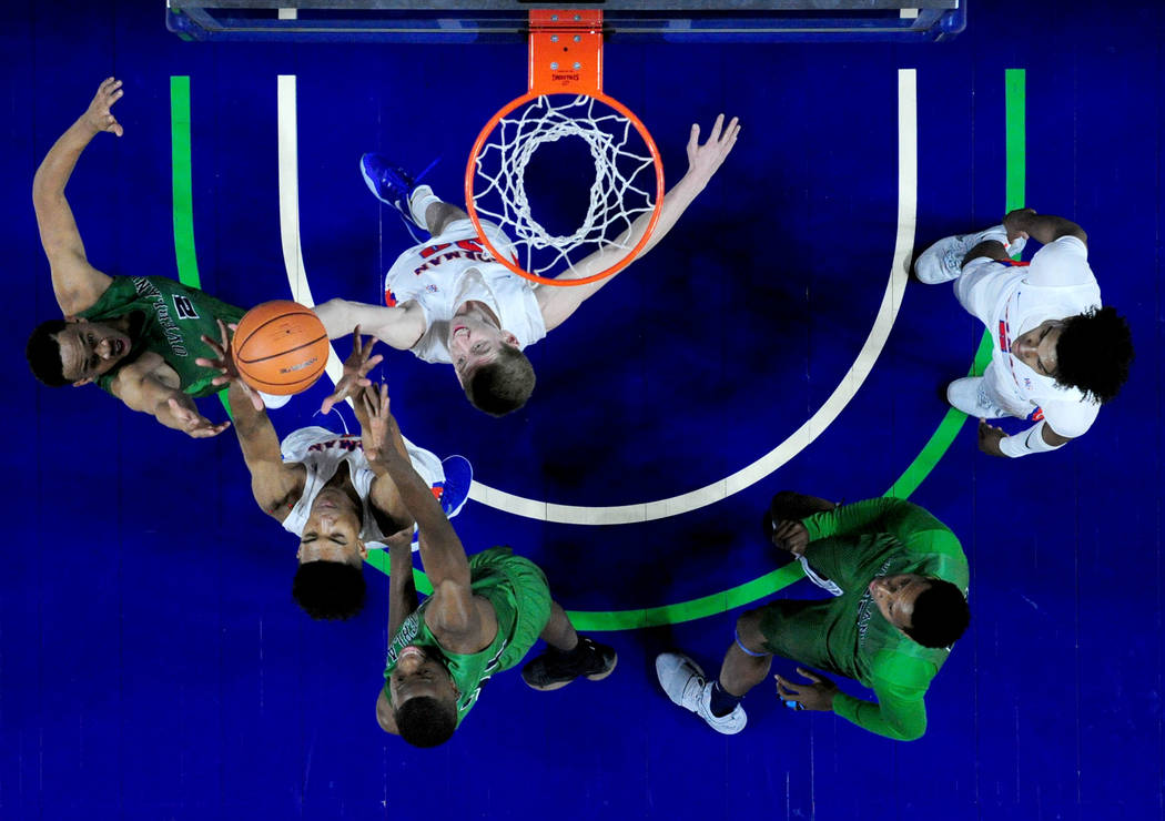 Bishop Gorman guard Noah Taitz (white, near the hoop) and center Isaiah Cottrell (white, second from left) go up for a rebound against Overland, Colo. guard Daijon Smith (2) and forward Laolu Oke  ...