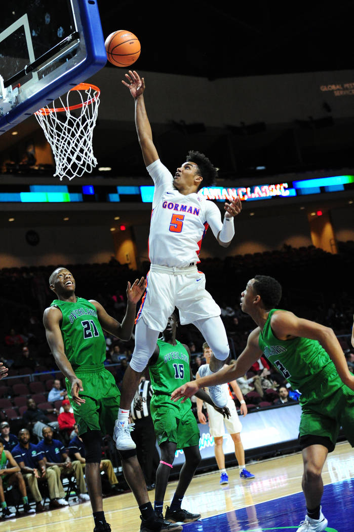 Bishop Gorman guard Jamal Bey (5) goes up for a shot in front of Overland (Colo.) forward Laolu Oke (21) during their prep basketball game at Orleans Arena in Las Vegas Wednesday, Dec. 20, 2017. J ...