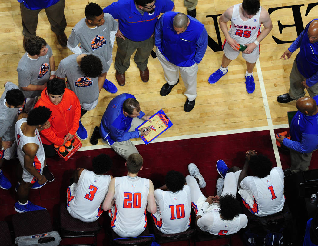 Bishop Gorman head coach Grant Rice, center, draws up plays durfing a time-out against Overland (Colo.) during their prep basketball game at Orleans Arena in Las Vegas Wednesday, Dec. 20, 2017. Jo ...