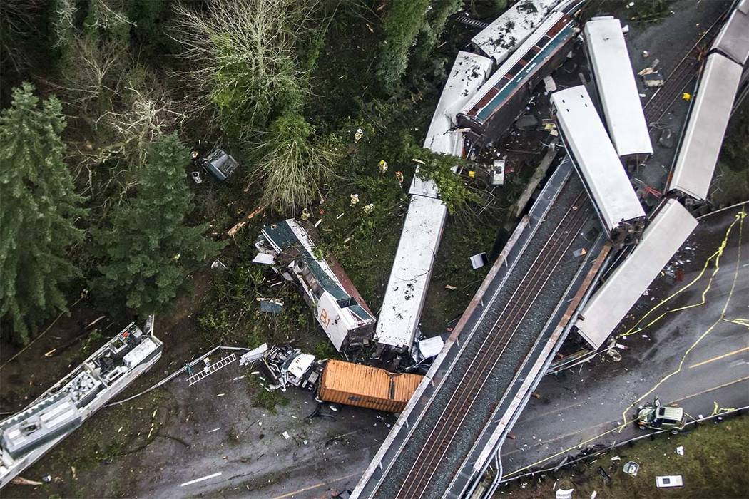 Cars from an Amtrak train that derailed above lie spilled onto Interstate 5, Monday, Dec. 18, 2017, in DuPont, Wash. The Amtrak train making the first-ever run along a faster new route hurtled off ...