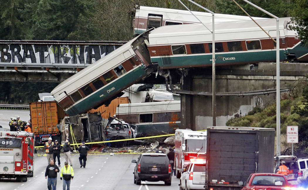 Cars from an Amtrak train lay spilled onto Interstate 5 below alongside smashed vehicles as some train cars remain on the tracks above Monday, Dec. 18, 2017, in DuPont, Wash. The Amtrak train maki ...