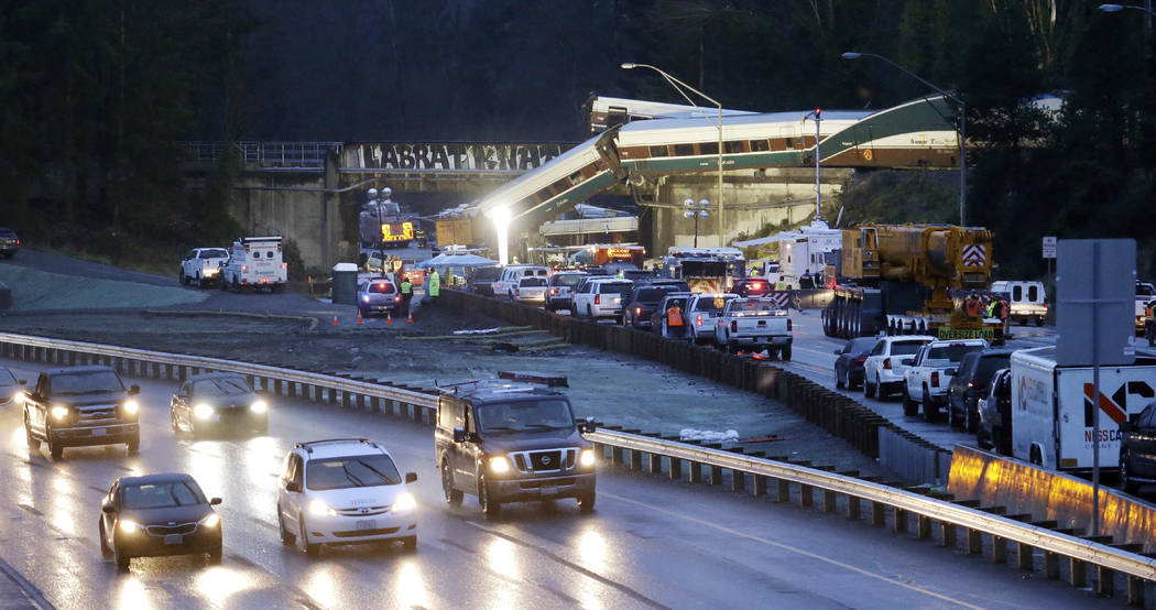 Traffic moves along northbound Interstate 5, left, as southbound lanes are filled with emergency vehicles near the scene of an Amtrak train crash Monday, Dec. 18, 2017, in DuPont, Wash. The Amtrak ...