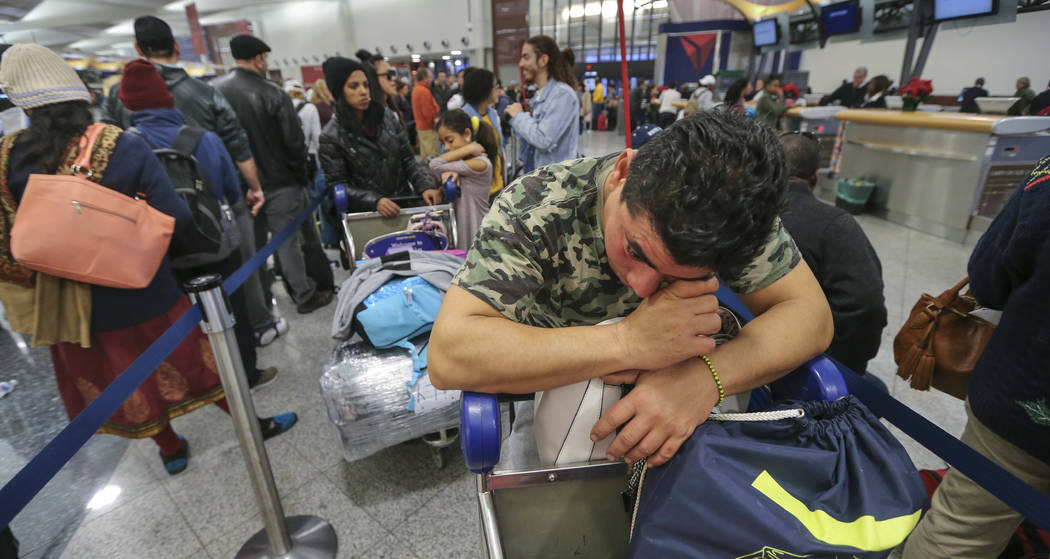 Alexis Canete rests on his luggage as he waits in the Delta ticket line to get back home to Cuba from his visit to Tennessee on Monday Dec. 18, 2017 at Hartsfield-Jackson International Airport in  ...