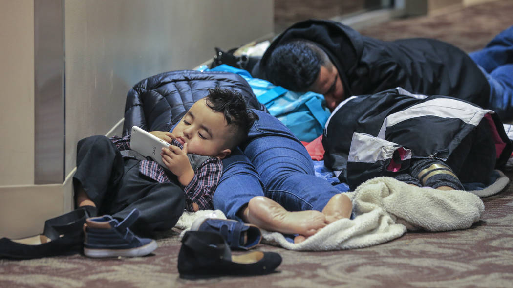 Kenneth Reyes, 2, watches phone cartoons as his parents, Lucas and Areli and sister, Yosselyn-11 sleep on the second floor of the atrium overnight into Monday morning, Dec. 18, 2017, at the airpor ...