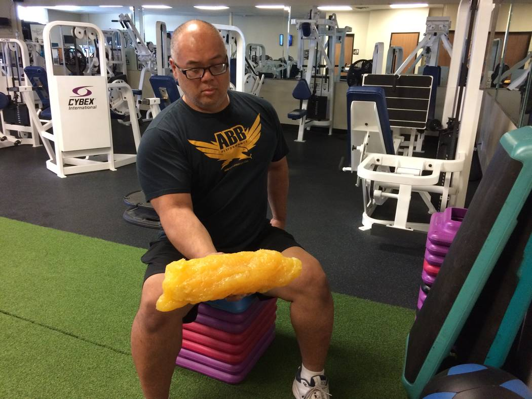 "Mel Fabros, certified trainer and owner/operator of Bodysport, holds a plastic model representing five pounds of fat. ""Imagine 20 of these, strapped all around the body,"" he said. His gym helps pe ..."