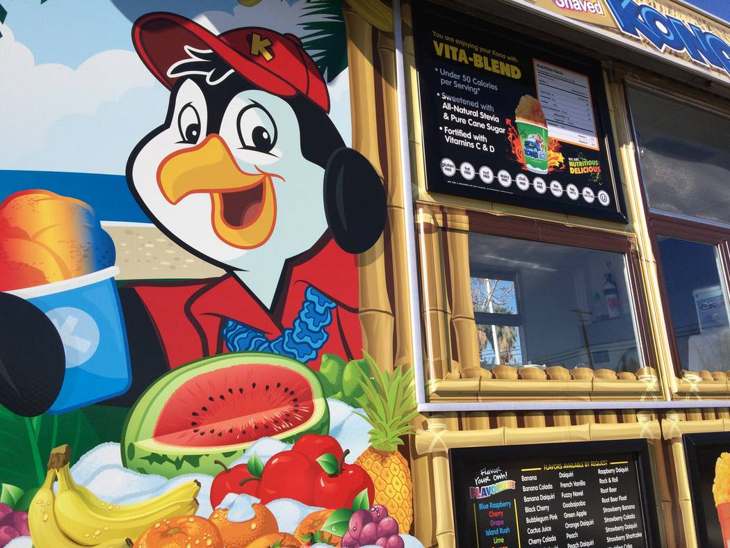Kona the penguin, seen Dec. 11, 2017, greets patrons to Larry and Sandy Smith's new business, a Kona Ice truck. The colorful truck cost $135,000, was outfitted with air conditioning and UV tinted  ...