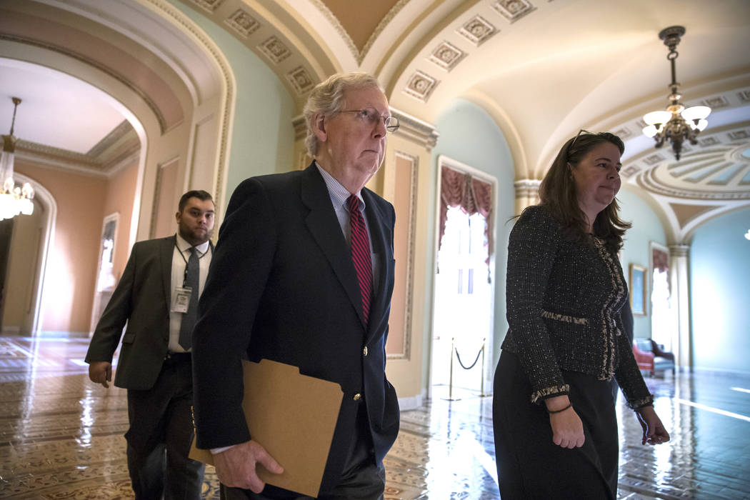 Senate Majority Leader Mitch McConnell, R-Ky., accompanied by Secretary for the Majority Laura Dove, walks to the chamber as Republicans in the House and Senate plan to pass the sweeping $1.5 tril ...