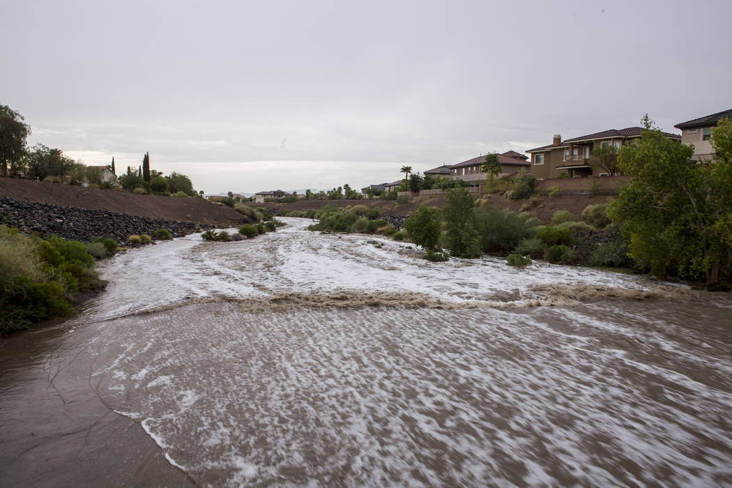 Flood waters rush through the Pittman Wash in Henderson during a monsoon rainstorm on Wednesday, July 19, 2017. Funding approved Tuesday would add flood control upstream, near the intersection of  ...