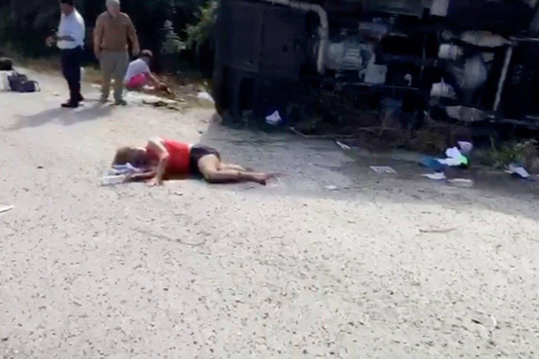 This video frame shows an injured woman lying on the road next to the overturned bus she was traveling in, in Mahahual, Quintana Roo state, Mexico, Tuesday, Dec. 19 2017. At least 12 people died w ...
