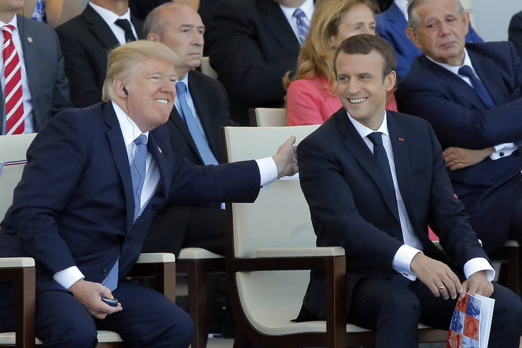 A Friday, July 14, 2017 file photo of French President Emmanuel Macron, right, and U.S. President Donald Trump attending the traditional Bastille Day military parade on the Champs Elysees, in Pari ...