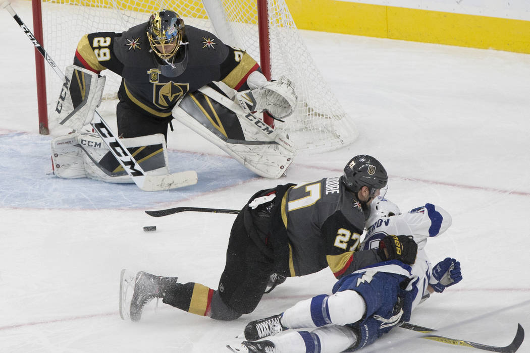 Golden Knights goaltender Marc-Andre Fleury (29) makes a save with the help of defenseman Shea Theodore (27) in the third period during Vegas' home matchup with the Lighting on Tuesday, Dec. 19, 2 ...