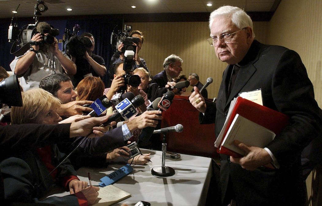 In this Tuesday, Nov. 12, 2002 file photo, Cardinal Bernard Law, right, departs a news conference during the second day of the U.S. Conference of Catholic Bishops annual meeting in Washington. An  ...