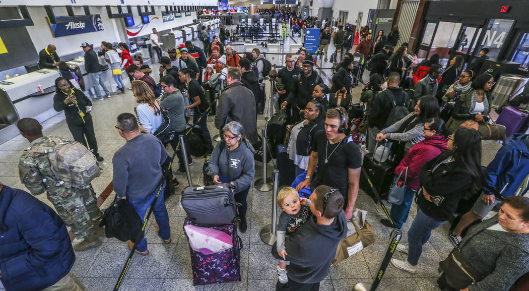 The ticket counters are swamped with travelers in the North terminal on Monday Dec. 18, 2017 at Hartsfield-Jackson International Airport in Atlanta, the day after a massive power outage brought op ...