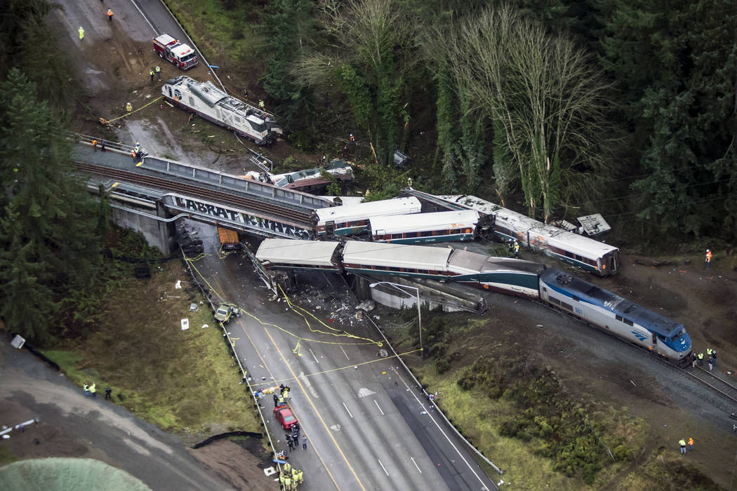 Cars from an Amtrak train that derailed lie spilled onto Interstate 5, Monday, Dec. 18, 2017, in DuPont, Wash. The Amtrak train making the first-ever run along a faster new route hurtled off the o ...