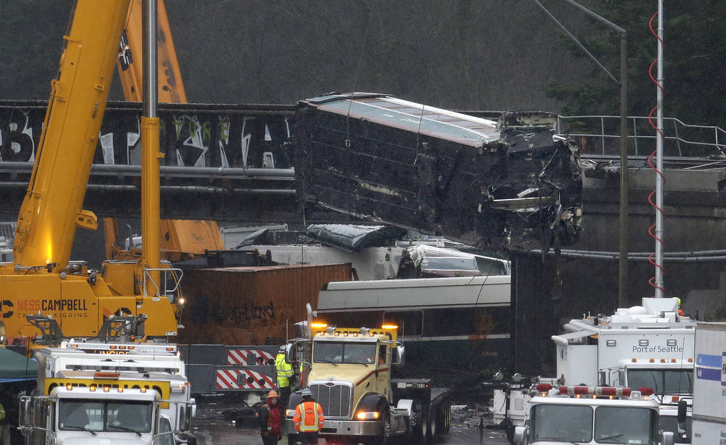 A damaged Amtrak train car is lowered from an overpass at the scene of Monday's deadly train crash onto Interstate 5 Tuesday, Dec. 19, 2017, in DuPont, Wash. Federal investigators say they don't y ...