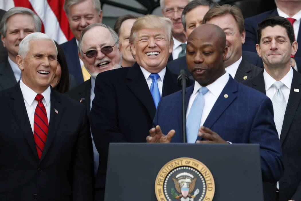 U.S. President Donald Trump laughs during remarks by U.S. Senator Tim Scott (R-SC) during an event with Republican lawmakers to mark passage of sweeping tax overhaul legislation at the White House ...