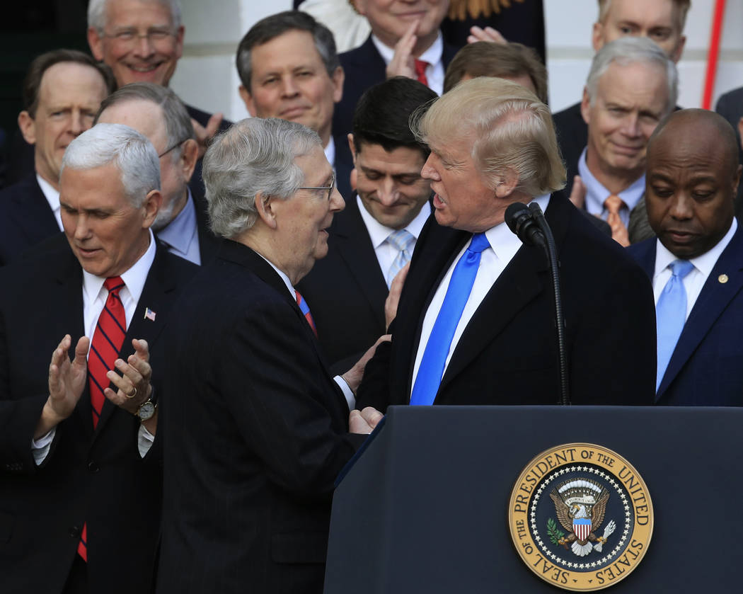President Donald Trump, shakes hands with Senate Majority Leader Mitch McConnell of Ky., during a tax bill passage event on the South Lawn at the White House in Washington, Wednesday, Dec. 20, 201 ...