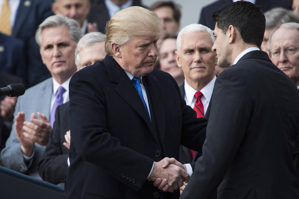 President Donald Trump, flanked by Speaker of the House Rep. Paul Ryan, R-Wis. and Chairman of the House Ways and Means Committee Rep. Kevin Brady, R-Texas, holds an example of what a new tax form ...