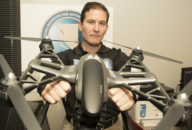 Dr. Chris Walach, director of operations of unmanned aviation for Nevada Institute for Autonomous Systems, poses with a Yuneec Q500 4K quadcopter following a flight demonstration at his office in  ...