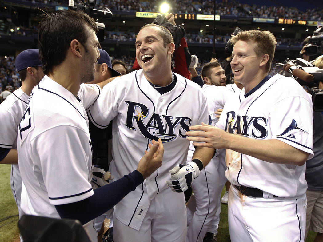 In this Sept. 29, 2011, file photo, Tampa Bay Rays' Evan Longoria, center, celebrates with teammates Sean Rodriguez, left, and Elliot Johnson after his home run that defeated the New York Yankees  ...