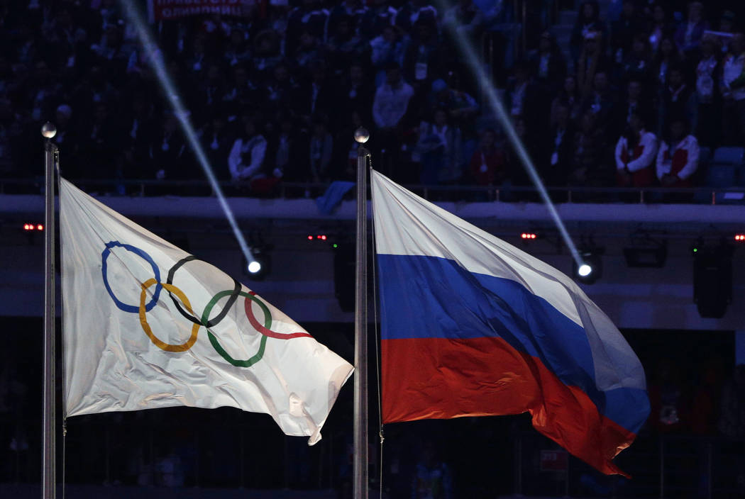 "In this Feb. 23, 2014 file photo, the Russian national flag, right, flies next to the Olympic flag during the closing ceremony of the 2014 Winter Olympics in Sochi, Russia. The word ""Russia"" will  ..."