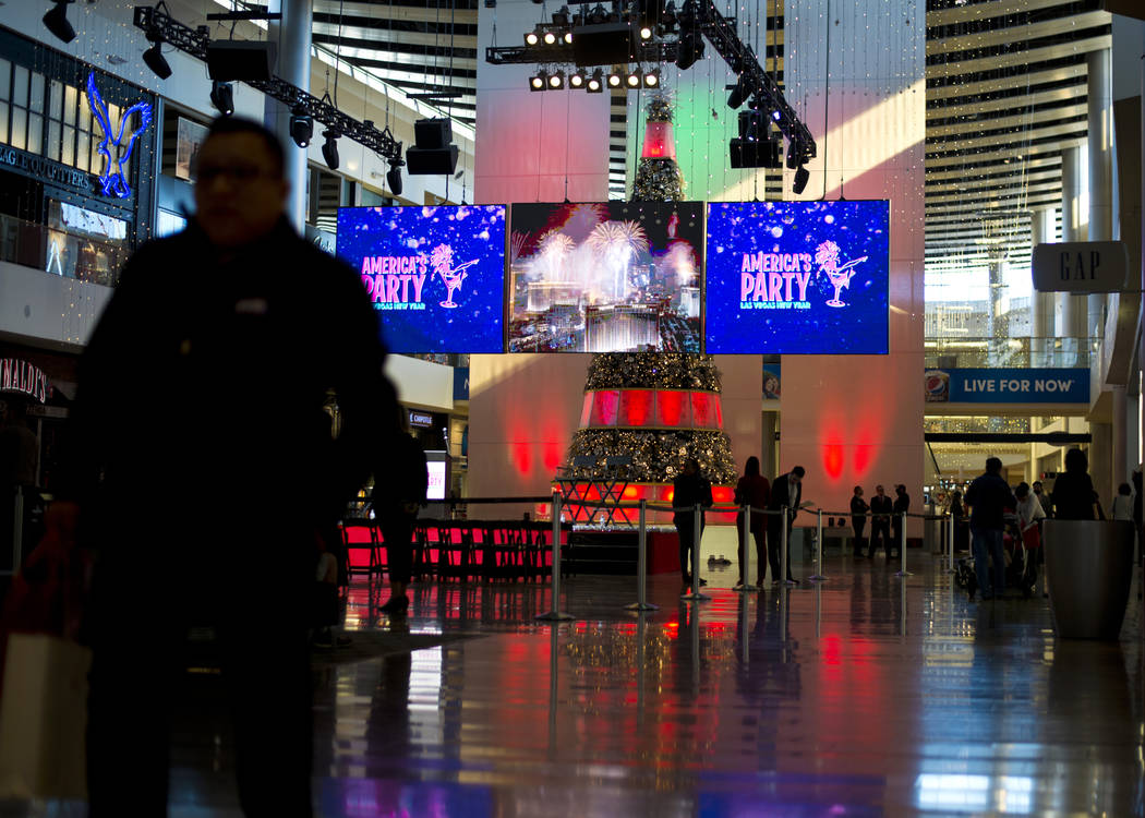 "People walk by during the ""America's Party"" news conference announcing details of Las Vegas New Year's Eve celebrations inside the Great Hall of the Fashion Show Mall on Thursday ..."
